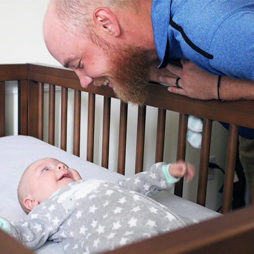 Father looking at baby in crib
