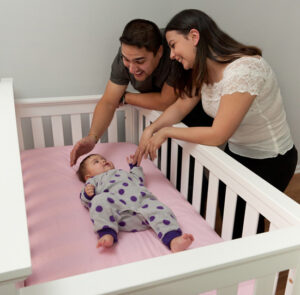Parents Placing Baby In Crib